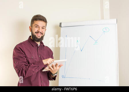 Young bearded man presenting by the flipchart - Stock Photo