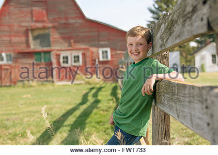 Young boy leaning on fence on rural property. - Stock Photo