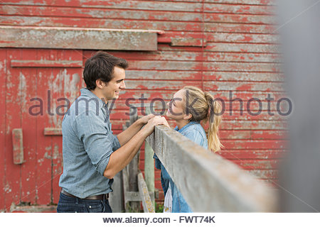 Young couple being affectionate in front of barn. - Stock Photo