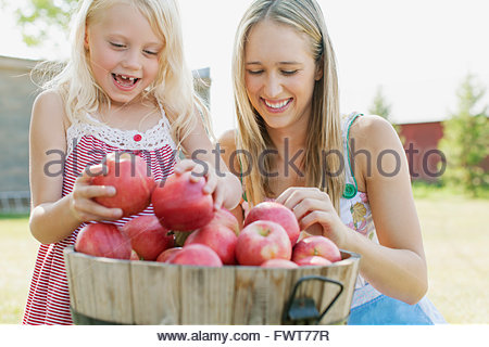 Mother and young daughter putting fresh apples in basket. - Stock Photo