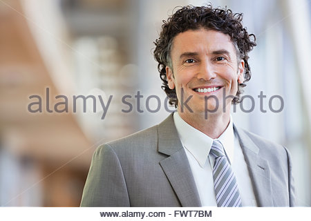 Portrait of mature businessman smiling in office - Stock Photo