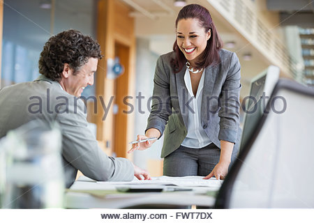 Happy business colleagues talking over blueprint at desk - Stock Photo