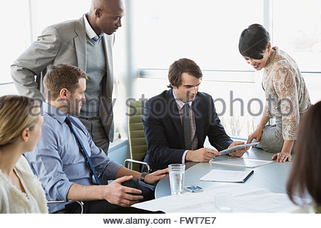 Businessman using digital tablet with colleagues at conference table - Stock Photo