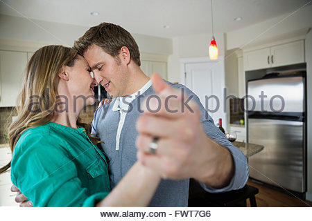 Romantic mid adult couple dancing in kitchen. - Stock Photo