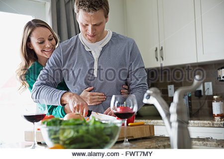 Wife embracing husband from behind as he prepares salad - Stock Photo