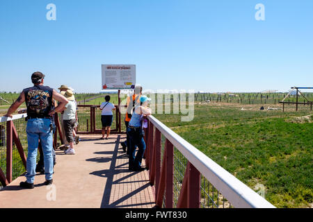 Visitors gaze over various animal enclosures along the viewing area at The Wild Animal Sanctuary in Colorado - Stock Photo