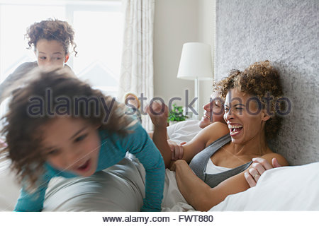 Daughters pouncing on parents bed. - Stock Photo