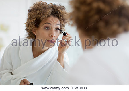 Woman applying make-up in mirror. - Stock Photo