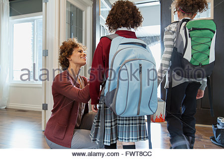 Mother sending daughters off to school. - Stock Photo