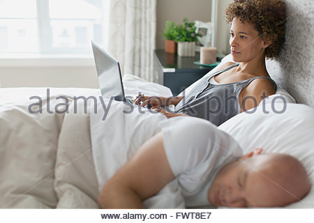 Woman using tablet computer in bed while husband sleeps. - Stock Photo