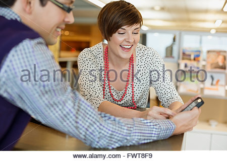 Businesswoman looking at smartphone with male colleague - Stock Photo
