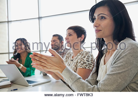 Business people applauding around conference table - Stock Photo
