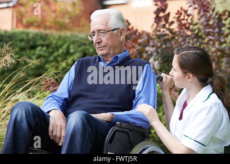 Nurse Comforting Senior Man In Wheelchair - Stock Photo