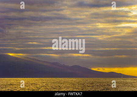 Shoulder of Haleakala seen at sunrise from a tour boat - Stock Photo