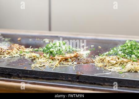 cooking of okonomiyaki japanese pizza - Stock Photo