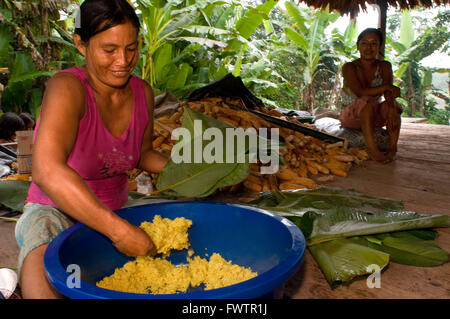 Woman preparing Juanes tamales of rice and chicken by traditional method in Timicuro I, Iqutios peruvian amazon, - Stock Photo