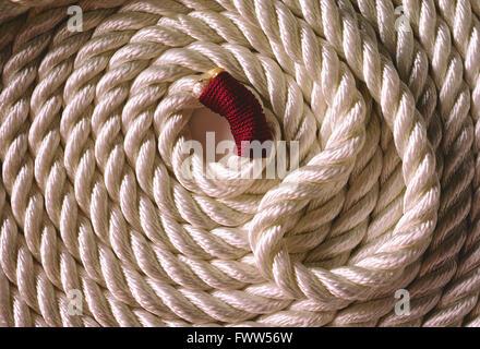 Heavy coiled white marina rope - Stock Photo