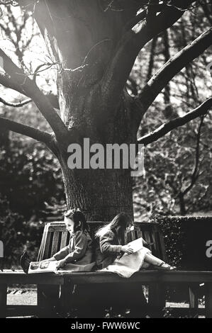 two little girls sisters sitting on bench under tree and read books - Stock Photo