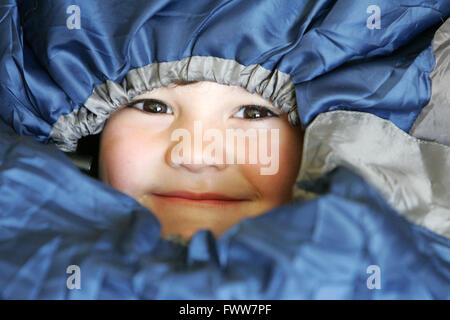 Young boy all tucked up in a sleeping bag - Stock Photo