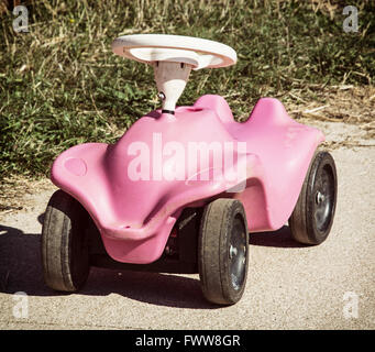 Cute pink toy car in outdoor. Playground theme. - Stock Photo