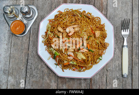 fried noodle dish on rustic tabletop - Stock Photo