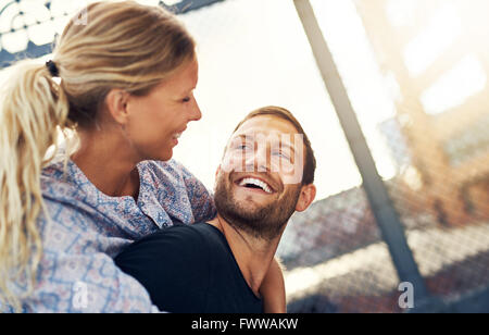 Couple Smiling At Each Other, Woman On Mans Back - Stock Photo