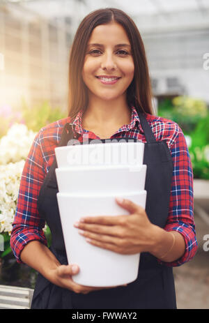 Pretty young worker in a floriculture business standing working in the greenhouse holding stacked plastic flower - Stock Photo