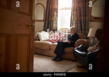 Senior Woman Sitting On Sofa Reading Book At Home - Stock Photo