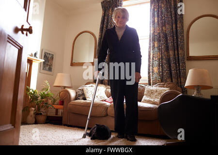 Portrait Of Senior Woman With Crutch Standing In Lounge - Stock Photo