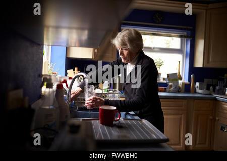 Senior Woman Doing Washing Up In Kitchen - Stock Photo