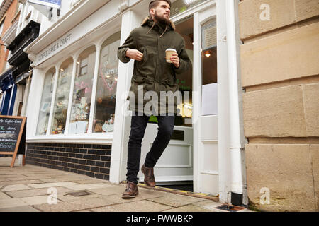 Male Customer Coming Out Of Cafe With Takeaway Coffee - Stock Photo