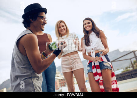 Outdoor shot of young man opening a bottle of champagne with female friends standing in background by the pool. - Stock Photo