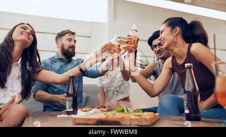 Group of friends toasting beers in a party while sitting around table. Multiracial friends hanging out on rooftop - Stock Photo
