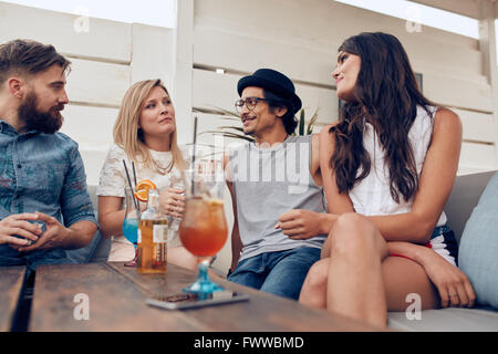 people around kitchen group of young friends chatting around kitchen table stock photo