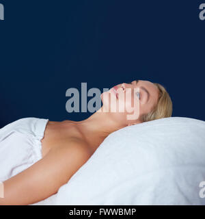 Indoor shot of attractive young woman lying on massage table. Caucasian woman wrapped in white towel lying on bed - Stock Photo