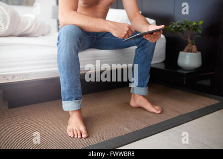 Cropped shot of a young man using digital tablet while sitting alone on the bed. - Stock Photo