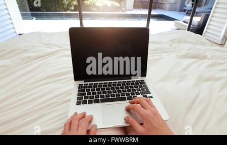 Closeup image of woman on a bed working on laptop computer. POV shot of woman relaxing in bedroom using laptop. - Stock Photo