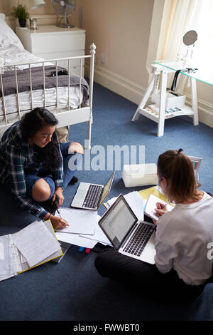 Two Female Students With Laptops Studying In Bedroom - Stock Photo