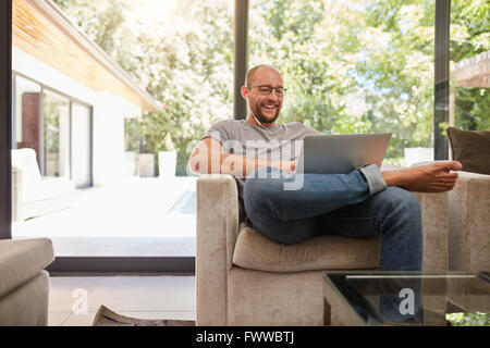 Indoor shot of a happy mature man having video call with laptop and earphones while sitting on the couch at home. - Stock Photo