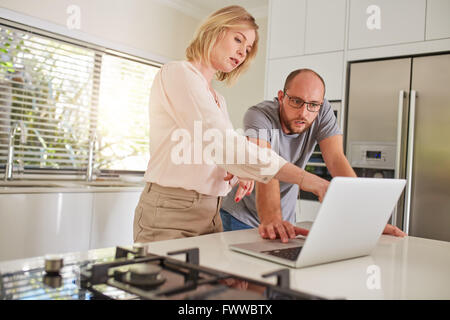 Portrait of mature couple working together on a laptop in the kitchen. Couple standing by the kitchen counter, with - Stock Photo
