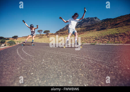 Young man and woman skateboarding on the road. Young couple practicing skating on a open road. - Stock Photo