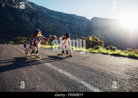 Best friends having fun with skateboard on open road. Young man and woman longboarding together on a sunny day. - Stock Photo