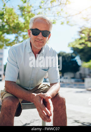 Portrait of handsome mature man sitting outdoors. Senior male tourist with sunglasses sitting outside in the city - Stock Photo