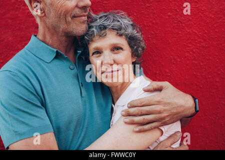 Portrait of happy mature woman embracing her husband against red background. Affectionate couple together against - Stock Photo