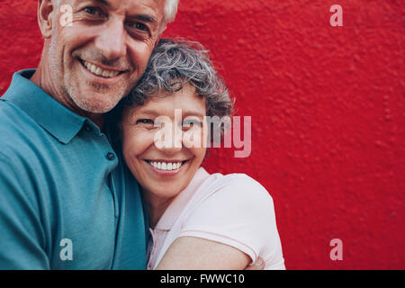 Portrait of cheerful middle aged couple embracing each other against red background. Mature man and woman together - Stock Photo