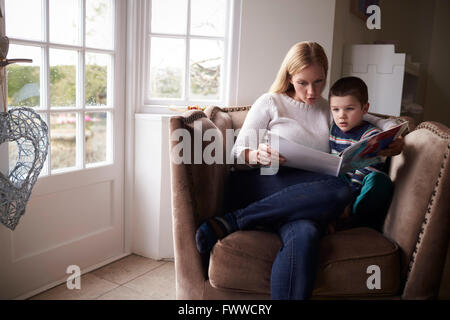 Mother Sitting In Chair At Home Reading Story To Son - Stock Photo