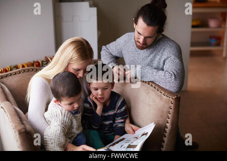 Parents Sitting In Chair At Home Reading Story To Sons - Stock Photo