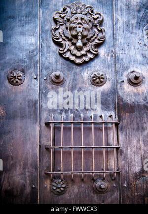 An ornate door knocker on a heavy wooden door at Iglesia de San Francisco in Antigua, Guatemala. - Stock Photo
