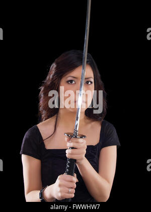 Young Asian woman holding Japanese sword in front of face
