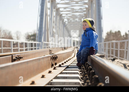 Portrait of a little boy sitting on the rails in the daytime. Belarus - Stock Photo
